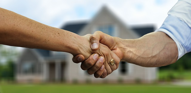 A Real Estate Agent and Homebuyer Shake Hands in Front of a Newly Purchased House in Shreveport Bossier, LA